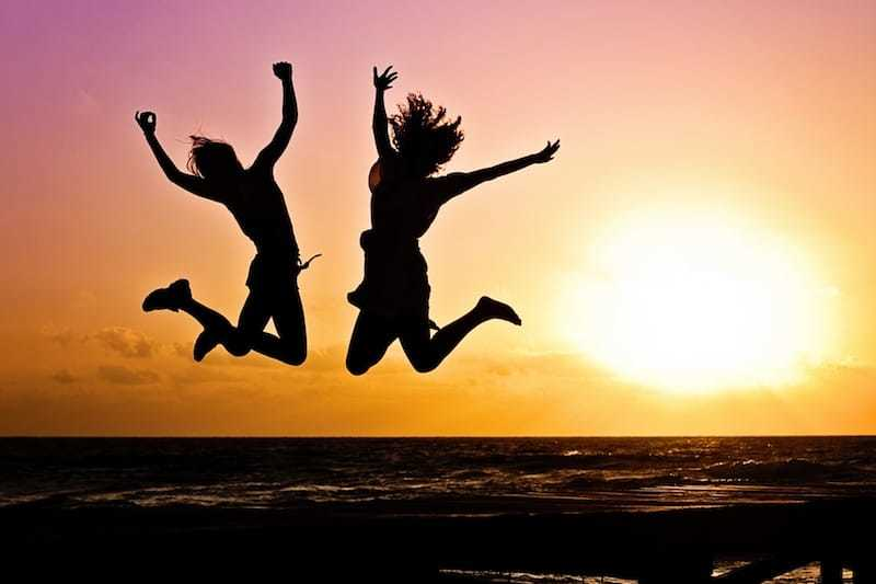 Happy Women jumping for joy at sunset