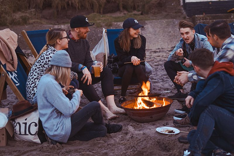 students happily chatting around a camp fire
