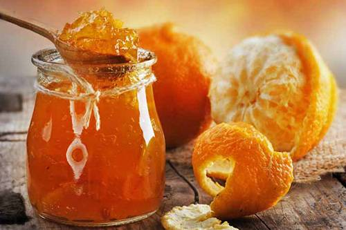 a jar of orange marmalade and peeled oranges