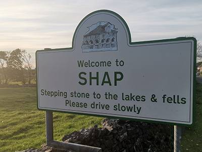 A road sign stating welcome to Shap, the stepping stones to the Lakes and Fells