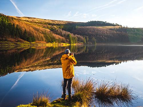 a photographer looking through his camera overlooking a dead calm lake
