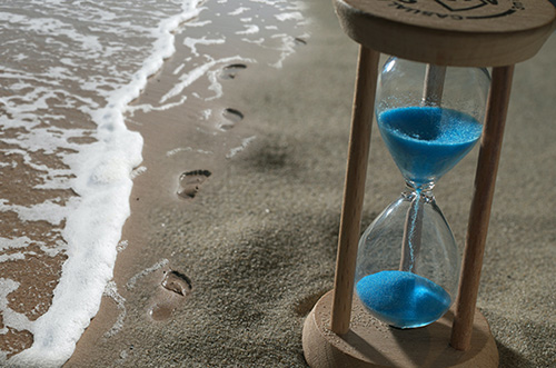 moments in time, an hour glass representing time on a shore line