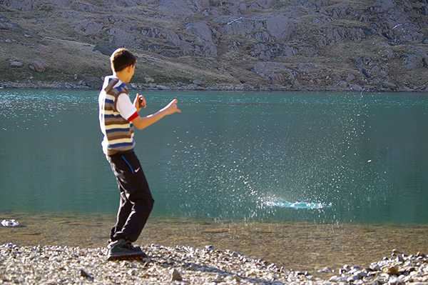 a person is skipping stones across a mountain lake, the water is very calm.